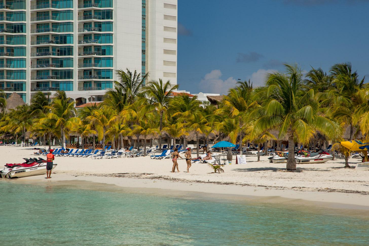 Strand in Cancun met wuivende palmen
